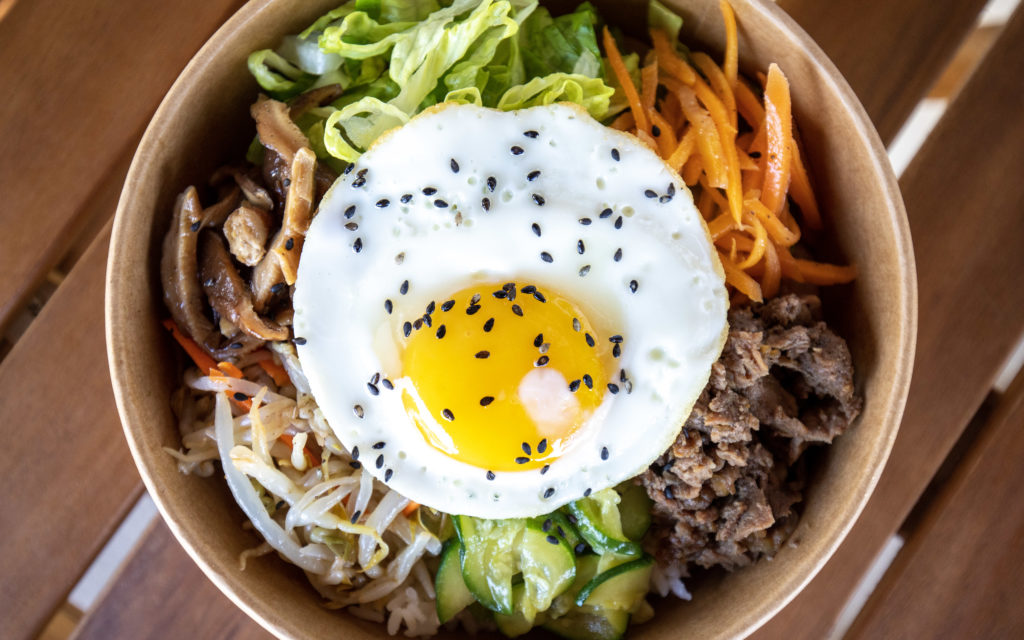 Bowl of Korean bibimbop with fried egg on top.