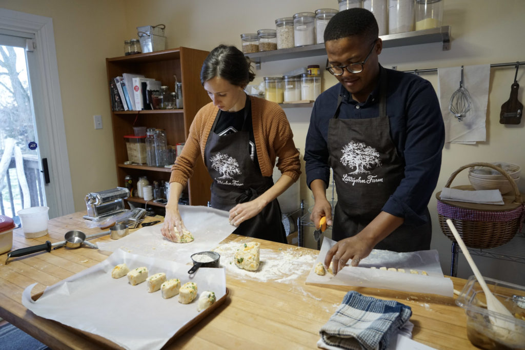 A woman and man cut biscuit dough in a country kitchen.
