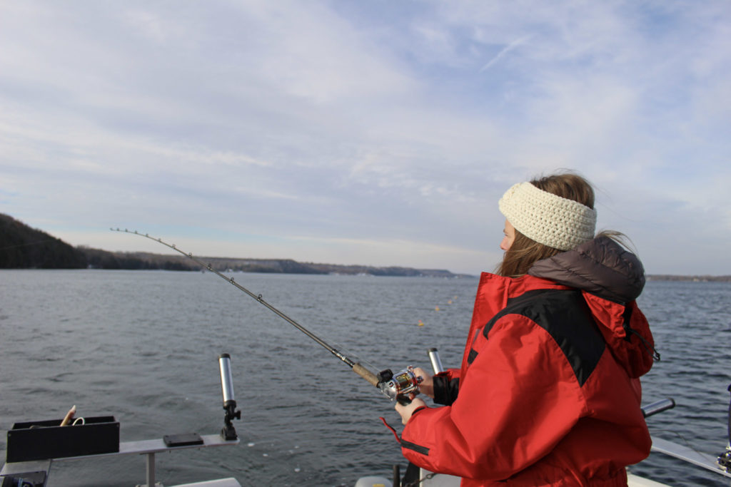 Woman with back to camera is fishing off the side of a boat in fall weather.