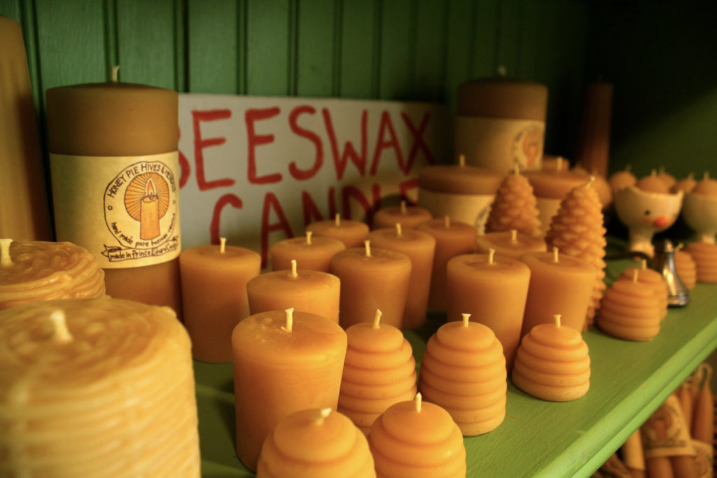 Two dozen yellow candles in front of a sign that says Beeswax Candles on a green shelf.