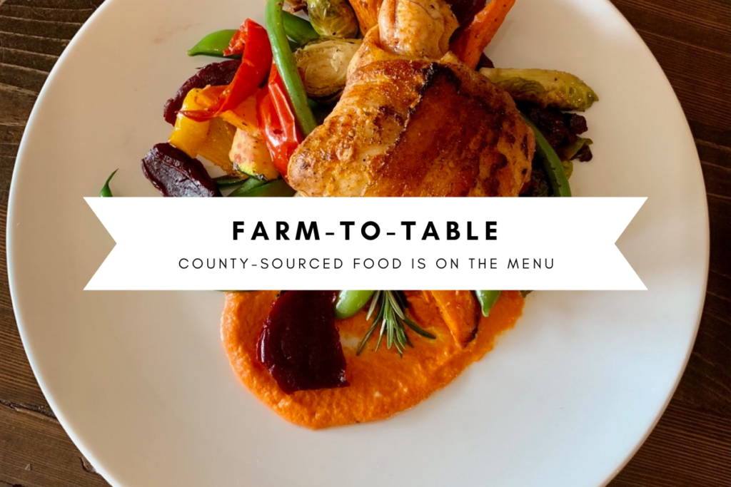 "Picture of a chicken and vegetable dish on a white plate with text ""Farm to Table: County Sourced Food is on The Menu"""