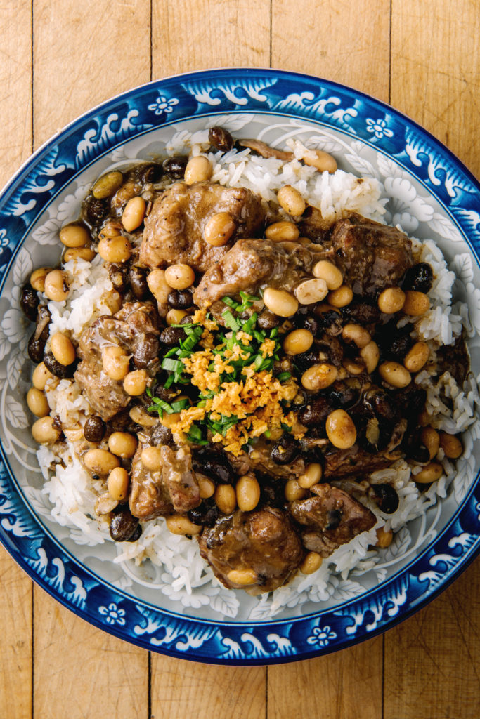 Overhead shot of beef and peanut curry over rice in a blue bowl.