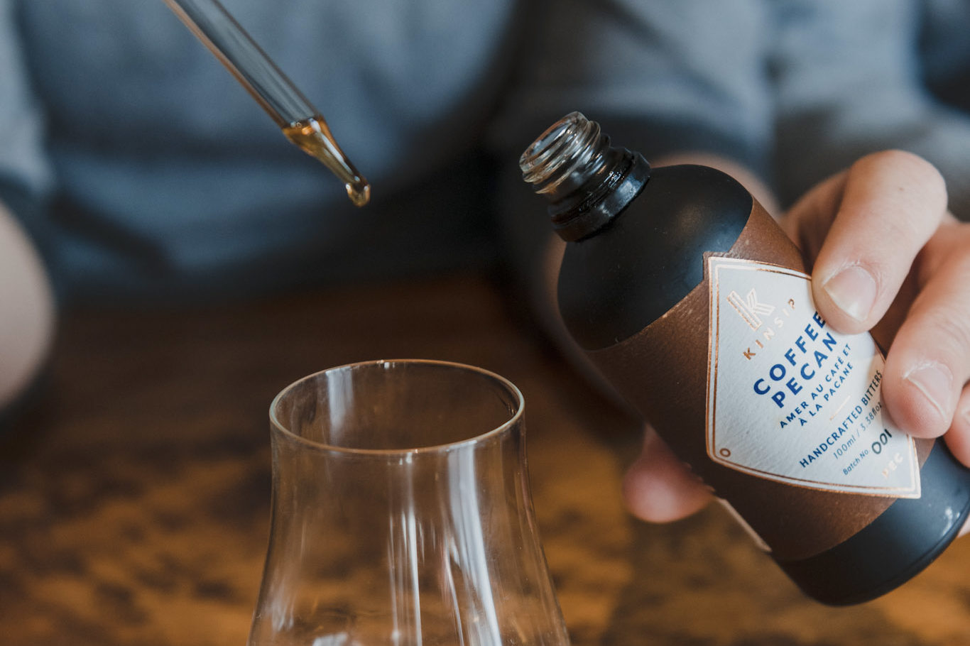 A dropper is used to put a drop of Coffee Pecan bitters from Kinsip Distillery into a glass