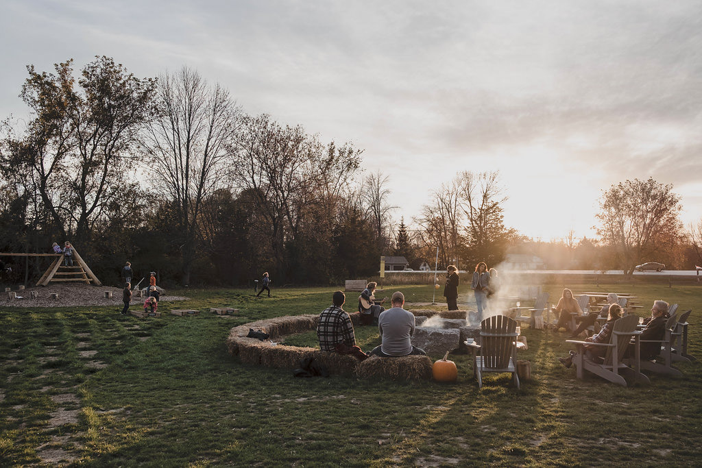A dozen adults gather around a large fire pit at sunset with children playing on wooden play structure in background