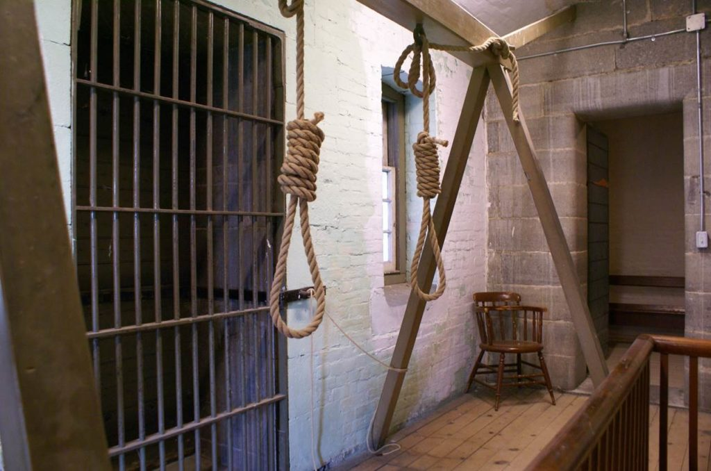 Image of two nooses hanging from a wooden frame in front of an old jail cell with metal bars.