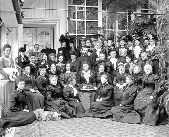 Image of approximately fifty women in long black Victorian-era dresses posed in front of a building.