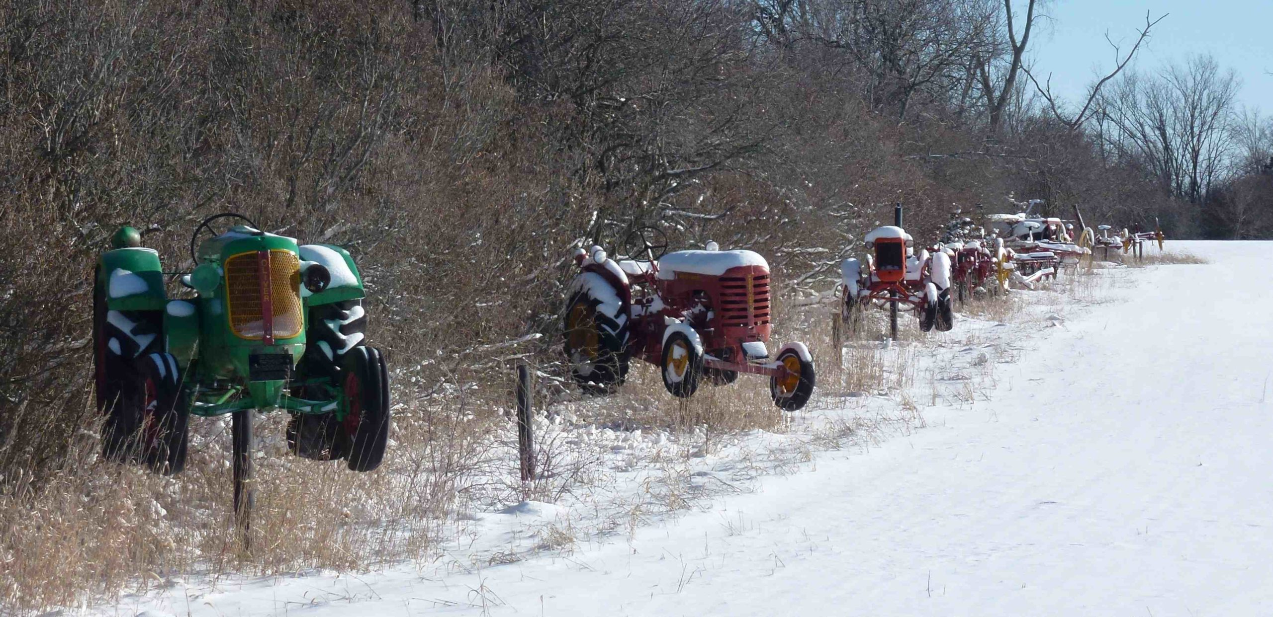 Three snow covered vintage tractors displayed along a snowy road. Bare trees in background.