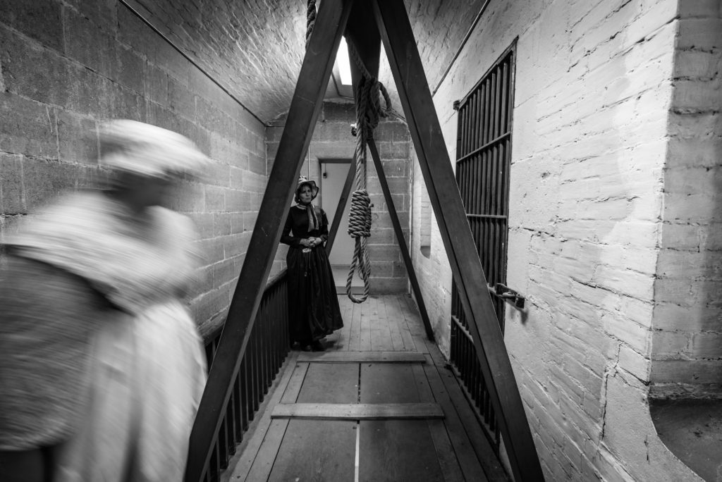 Photo of a woman in historical dress behind a wooden gallows. A ghostly, blurred figure in the foreground.