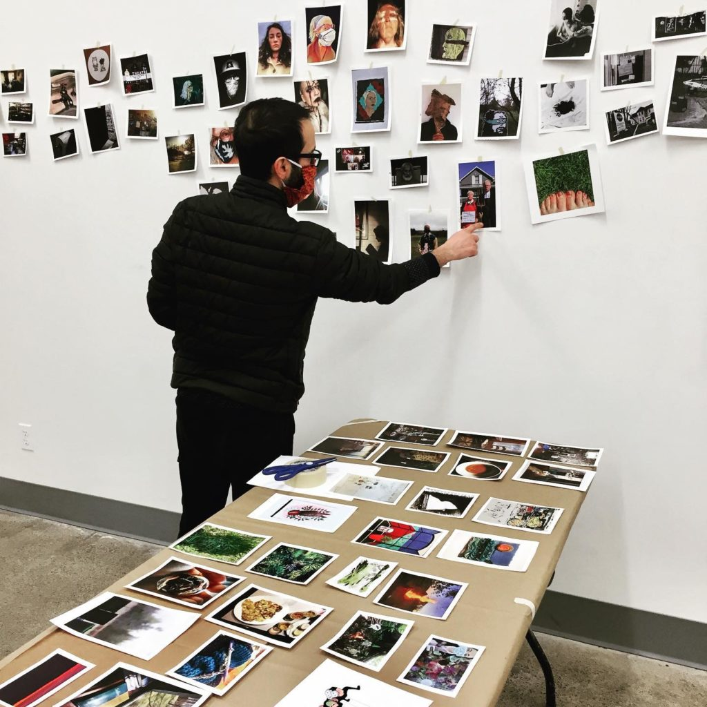 Artist Mehdi Agahi, wearing a mask, organizes images of artwork by taping them on a wall. A table with more art images in the foreground.