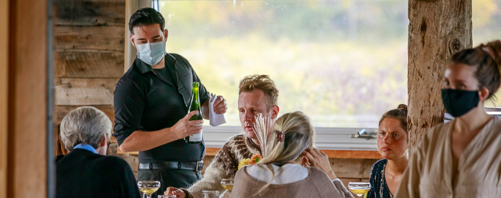 Image of four people seated at in a rustic restaurant. A male server in a mask holding a wine bottle speaks to them. A female server in COVID-19 mask in the foreground.