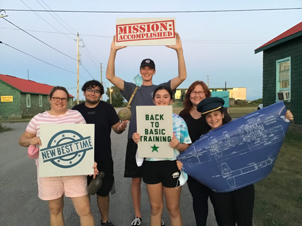 A group of six celebrate their escape from Escape Camp Picton's game with signs that say Mission Accomplished, New Best Time and Back to Basic Training.