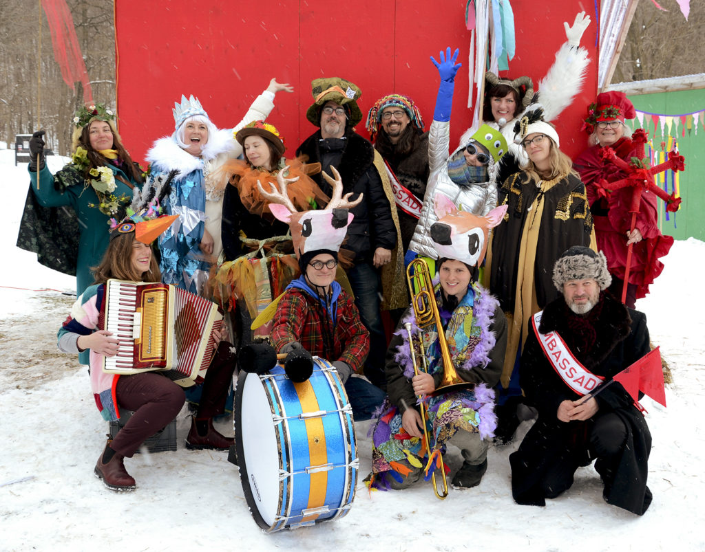 Photograph of a dozen individuals gathered in front of an ICE BOX hut in winter. They are wearing costumes, animal heads and carrying musical instruments and flags.