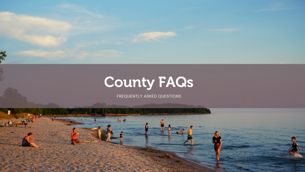 Image of Sandbanks Beach at sundown with bathers in the water and people relaxing on land. Text on image says County FAQs