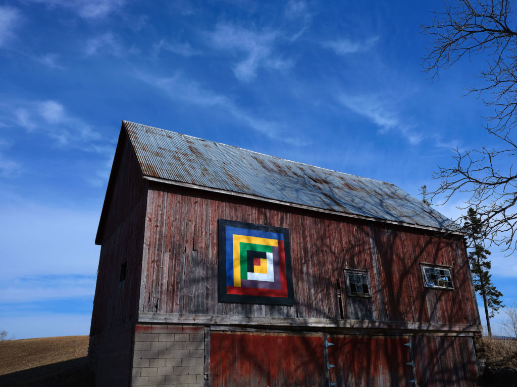 Red barn against a blue sky with a brightly coloured barn quilt above the barn door.