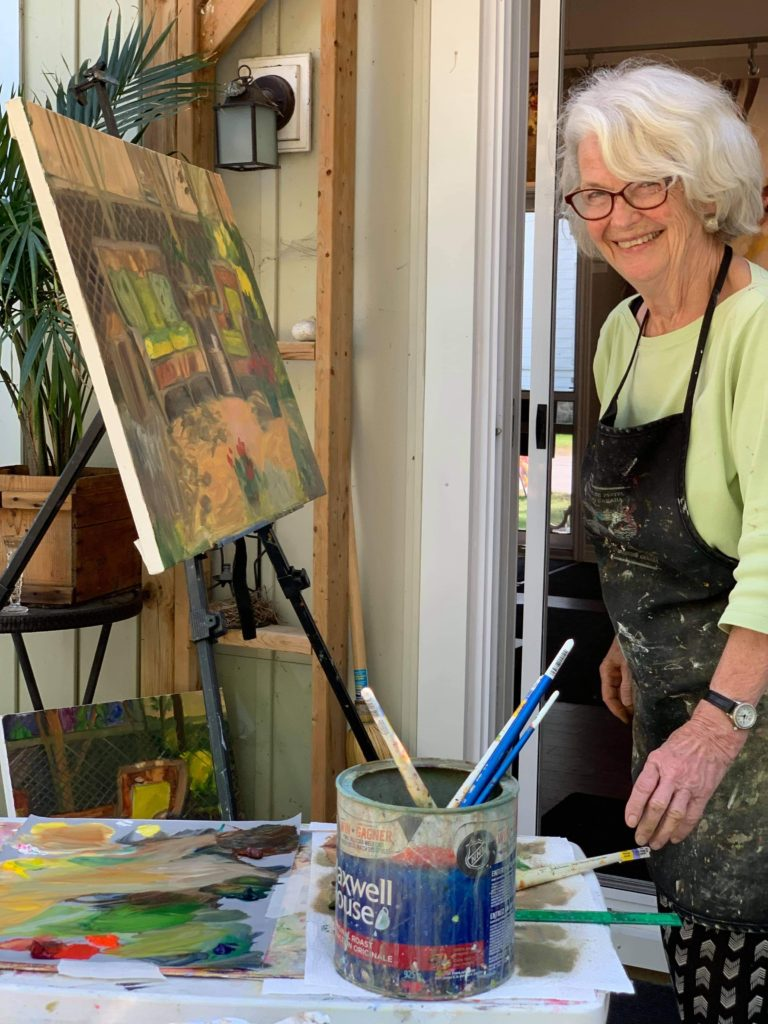 County artist Pamela Carter looking to her left and smiling at the camera wearing a lime green shirt and black painting smock. In front of her is an easel and canvas featuring a work-in-progress painting. In the foreground is a coffee tin filled with paint brushes and a palette of blended paints, the same colours as in the piece on the easel. 