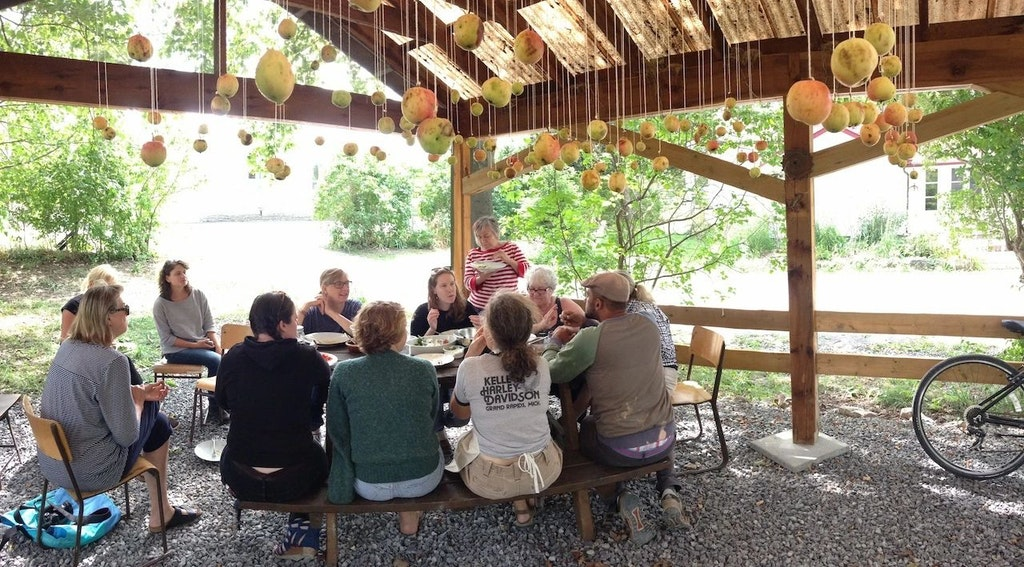Diners gather around a table under a pergola with hundreds of objects hanging from the ceiling on string above.